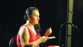 De jonge vrouw in een rode kleding voor een spiegel met een borstel zet schaduw op de oogleden stock footage