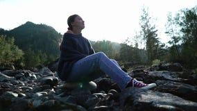 De jonge vrouw in een sweater zit op de stenen in berg in zonnige dag Silhouet stock video