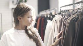 De jonge vrouw in een T-shirt kiest kleren in een opslag stock video