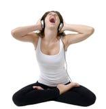 De jonge vrouw in een yoga stelt met hoofdtelefoons. Stock Fotografie