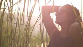 De jonge vrouw in een zwarte kleding en zonnebril maakt haar backlight bij zonsondergangachtergrond recht stock footage
