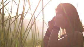 De jonge vrouw in een zwarte kleding zet op zonnebrilzonsondergang stock video