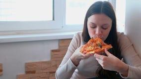 De jonge vrouw eet een plak van eigengemaakte pizza stock videobeelden