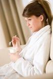 De jonge vrouw eet yoghurt voor ontbijt royalty-vrije stock foto