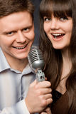 De jonge vrouw en de glimlachende man zingen in microfoon Stock Fotografie