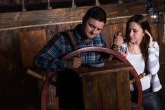 De jonge vrouw en de man bevinden zich bij het roer van het schip en bekijken Th royalty-vrije stock fotografie