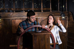De jonge vrouw en de man bevinden zich bij het roer van het schip en het proberen aan royalty-vrije stock afbeelding
