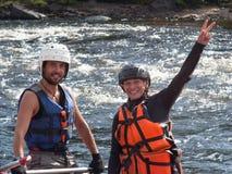 De jonge vrouw en de man gekleed in reddingsvesten en helmen zijn dicht langs en glimlach Stock Foto's