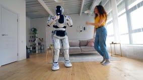 De jonge vrouw en een cyborg dansen gelukkig stock footage