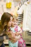 De jonge vrouw en haar dochter die bij de kinderen` s kleren glimlachen winkelen Royalty-vrije Stock Afbeelding