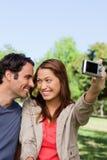 De jonge vrouw en haar vriend bekijken elkaar terwijl zij a neemt Stock Fotografie