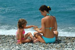 De jonge vrouw en het kind zitten op een strand Royalty-vrije Stock Afbeelding