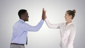 De jonge vrouw en de jonge man in formele kleding geven hoogte vijf op gradiëntachtergrond stock foto