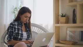De jonge vrouw freelancer werkt met laptop zitting in flat stock video
