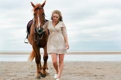 De jonge vrouw gaat dichtbij een paard stock foto