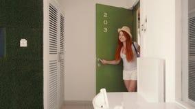 De jonge vrouw gaat met haar koffer binnen in haar nieuwe flat stock videobeelden