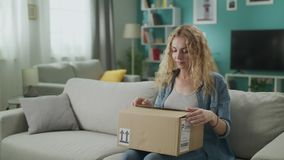 De jonge vrouw gaat zijn woonkamer met het pakket van de kartondoos in, begint het te openen stock footage