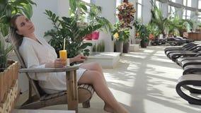 De jonge vrouw gaat zitten leunstoel en drinkt sap in kuuroordstreek stock videobeelden