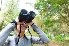 De jonge vrouw gebruikt binoculair Royalty-vrije Stock Afbeeldingen