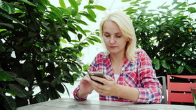 De jonge vrouw gebruikt de telefoon in een koffie Zit op het de zomerterras in Graz, Oostenrijk stock videobeelden