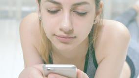 De jonge vrouw gebruikt een geschiktheid app op haar smartphone stock videobeelden