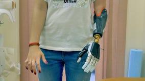 De jonge vrouw gebruikt innovatief robotachtig bionisch wapen 4K stock footage