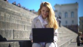 De jonge vrouw gebruikt laptop op de treden in het centrum van de stad stock video