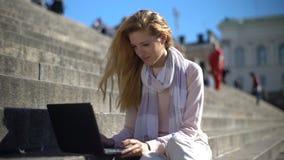 De jonge vrouw gebruikt laptop op de treden in het centrum van de stad Langzame Motie stock video