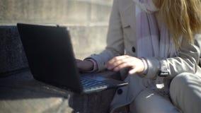 De jonge vrouw gebruikt laptop op de treden in het centrum van de stad Langzame Motie stock videobeelden