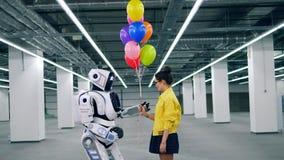 De jonge vrouw geeft vele kleurrijke ballons aan haar vriend cyborg stock videobeelden