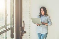 De jonge vrouw gekleed in blauw overhemd bevindt zich in ruimte dichtbij witte muur en gebruikt laptop Het Hipstermeisje controle stock foto