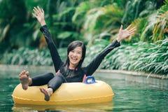 De jonge vrouw geniet van buizenstelsel bij luie rivierpool stock foto