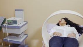 De jonge vrouw geniet van de procedure van magnetotherapy stock video