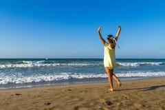 De jonge vrouw geniet van tijd op een strand bij schemer Stock Afbeelding