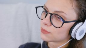 De jonge vrouw in glazen en hoofdtelefoons is luisterend een muziek, gezichtsclose-up stock footage