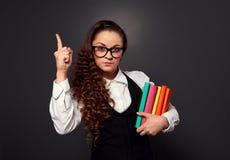 De jonge vrouw in glazen met stapel van boeken maakt aandachtsteken Stock Afbeelding