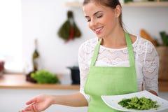 De jonge vrouw in groene schort kookt in een keuken De huisvrouw biedt verse salade aan Stock Fotografie
