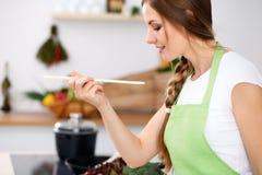 De jonge vrouw in groene schort kookt in een keuken De huisvrouw proeft de soep door houten lepel Stock Afbeelding