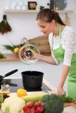 De jonge vrouw in groene schort kookt in een keuken De huisvrouw proeft de soep door houten lepel stock afbeeldingen