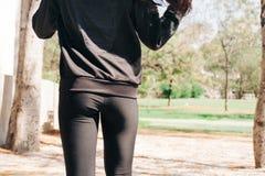 De jonge vrouw in gymnastiek kleedt erachter het aanstoten van en het nemen van een gang van in het park - in uitstekende toon Stock Fotografie