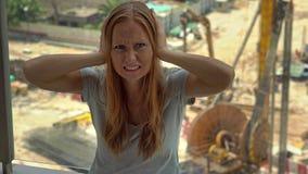 De jonge vrouw in haar die flat lijdt aan lawaai door de bouwwerf buiten het venster wordt geproduceerd stock footage