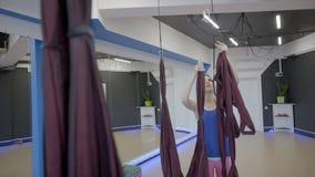 De jonge vrouw hangt stoffenhangmat in studio stock footage