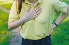 De jonge vrouw heeft een borstpijn stock afbeeldingen