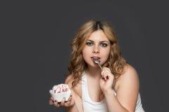 De jonge vrouw heeft een lepel in haar open mond Stock Foto