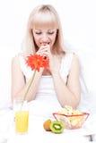 De jonge vrouw heeft een ontbijt royalty-vrije stock afbeelding