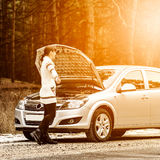 De jonge vrouw heeft een probleem met haar auto op de weg Stock Afbeelding