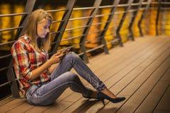 De jonge vrouw heeft goed nieuws bij smartphone stock fotografie