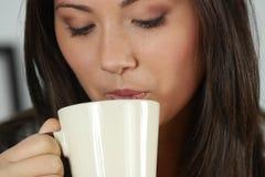 De jonge vrouw heeft haar thee/koffie Royalty-vrije Stock Foto's