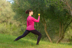 De jonge vrouw heeft pret in openlucht met gewichtheffen in het park Royalty-vrije Stock Foto