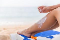 De jonge vrouw heeft rust op sunbed bij het strand en beschermt haar huid van toepassing zijnd sunblock op haar been royalty-vrije stock afbeeldingen